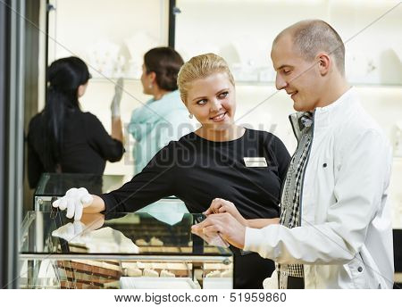 Sales assistant in shop demonstrating jewelry to young man customer during gift selecting