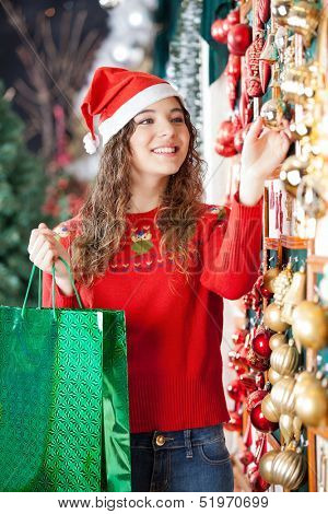 Happy woman in Santa hat with shopping bag buying Christmas ornaments at store