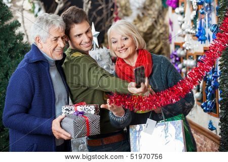 Happy family of three taking selfportrait through cellphone at Christmas store