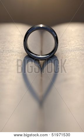 Wedding Ring Casting A Heart Shadow Between Pages Of A Book