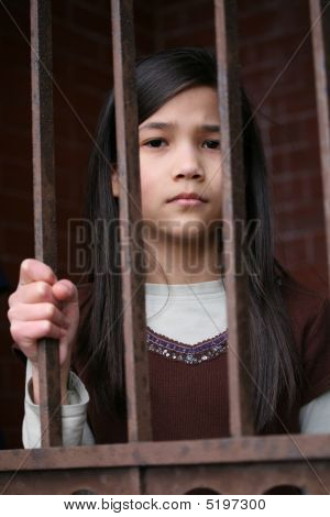 Unhappy Girl Standing Behind Bars