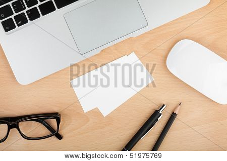 Blank business cards with supplies on wooden office table