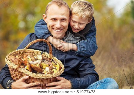 Father and son are happy that they have found a basket full of mushrooms