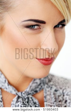 Beautiful blonde woman who is wearing a greyish blouse smiles with a smirk