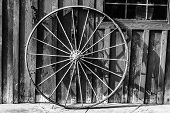 stock photo of wagon wheel  - An old rusty wagon wheel leaning on a barn wall in black and white - JPG