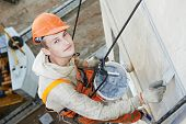 image of mortar-joint  - Portrait of Facade plasterer at outdoor wall renovation making off joints - JPG