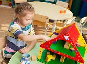 Child in kindergarten. Kids in nursery school. Girl playing at infant school. Game