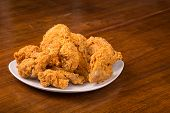 pic of wood pieces  - A white plate of fresh hot crispy fried chicken on a wood table - JPG