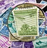 pic of iwo  - A closeup of a magnifying glass enlarging the 1945 Iwo Jima stamp in a pile of old stamps. ** Note: Slight blurriness, best at smaller sizes - JPG