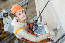 picture of mortar-joint  - Portrait of Facade plasterer at outdoor wall renovation making off joints - JPG