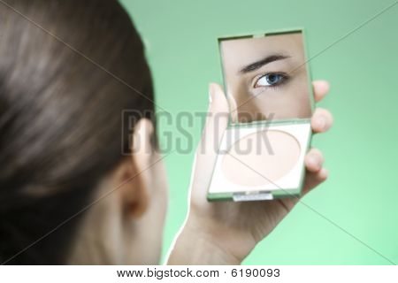 Young Woman Looking Into A Mirror To Check Her Make Up