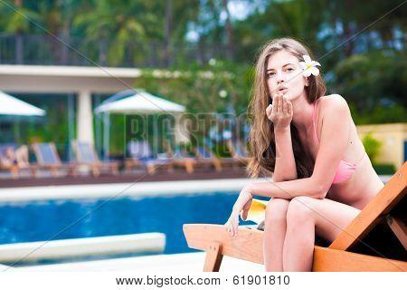 beautiful young woman in bikini on chaise-longue blowing air kiss