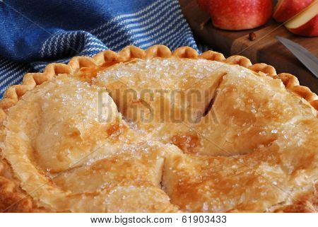 Freshly baked apple pie with sliced apple and knife on wooden cutting board in background.  Rustic still life with natural, directional lighting and shallow dof.