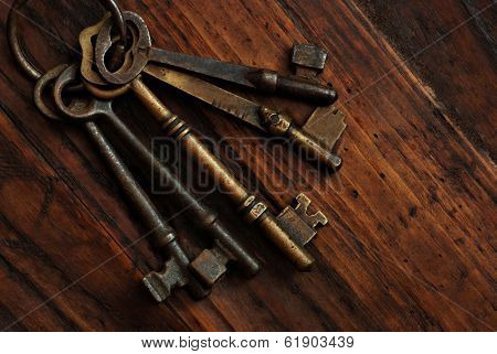 Antique skeleton keys on rustic dark wood background.  Low key still life with directional natural lighting.