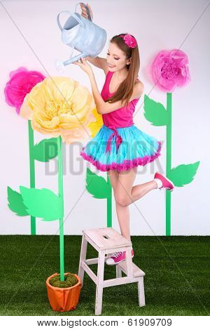 Beautiful young woman in petty skirt watering flower on decorative background