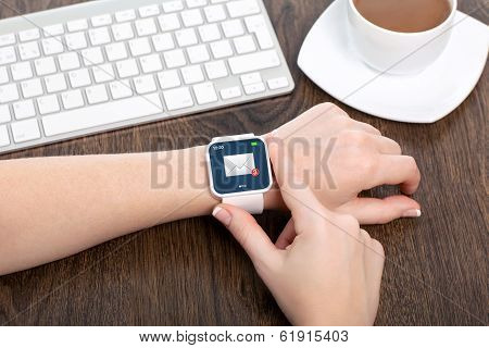 Female Hand With Smartwatch With Email On The Screen In An Office