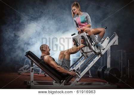 Man weightlifter doing leg presses with his trainer up on simulator