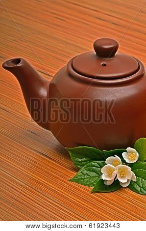 Clay Brown Teapot And Jasmine Flower On The Wood