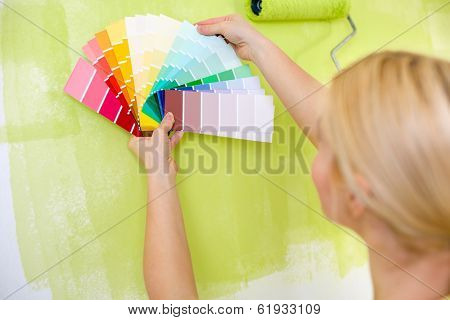 Woman with scale of paint swatches choosing color