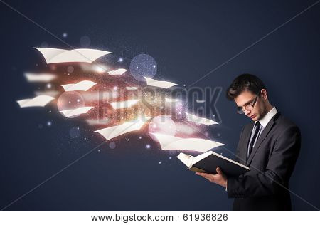 Young guy reading a book with flying sheets coming out of the book, magical reading concept