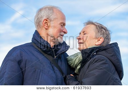 Elderly Couple Embracing And Celebrating The Sun