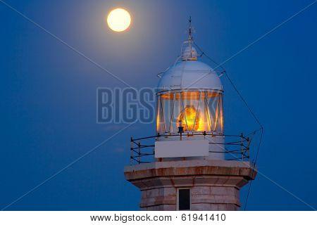 Ciutadella Menorca Punta Nati lighthouse with moon shining in sky