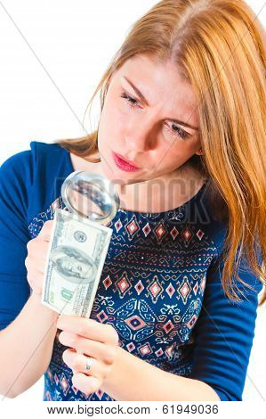 Girl Carefully Considering The Money Through A Magnifier
