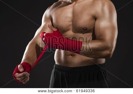 Portrait of a body combat athlet aplying tape on the hands