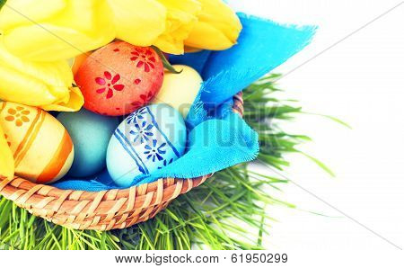 Basket Of Easter Eggs And Tulips On White