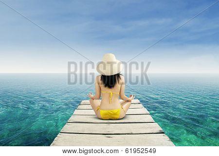 Woman Meditating At Serene Beach