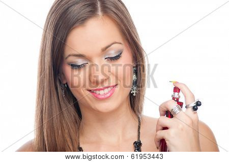 Beautiful brunette smiling and applying perfume on her neck, isolated on white