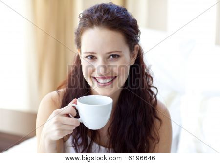 Smiling Woman Drinking A Cup Of Coffee In Bedroom