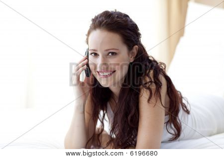 Smiling Woman In Bed Talking On Phone