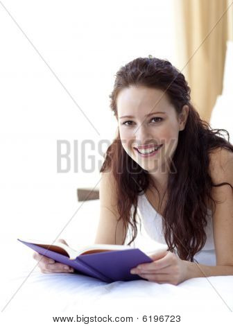 Beautiful Woman In Bed With A Book Smiling At The Camera