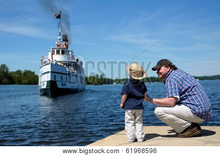 Father And Son Watch The Ship Come To Port