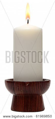 burning candle in vintage wooden candle holder.
