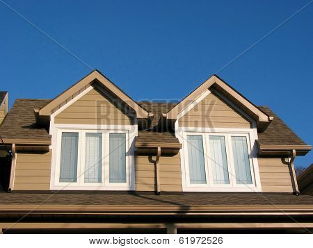 Fragment of a new custom built house on the background of bright blue sky