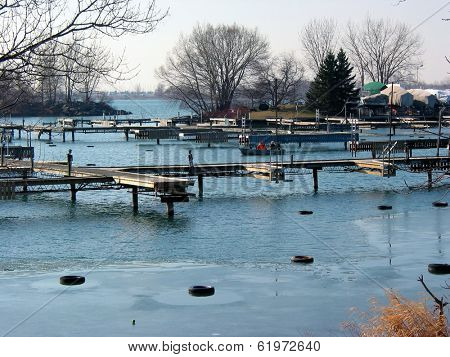 Sailboats drydocked next to the docks in a harbor on half frozen lake