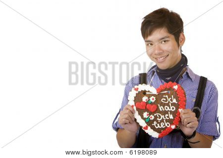 Young happy man holding Oktoberfest gingebread heart