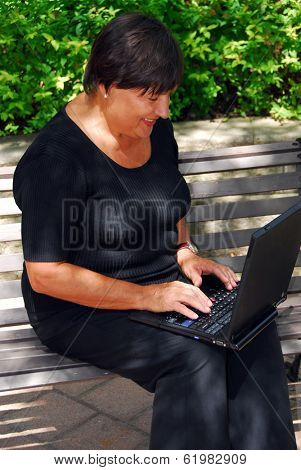 Mature woman typing on portable computer outdoor