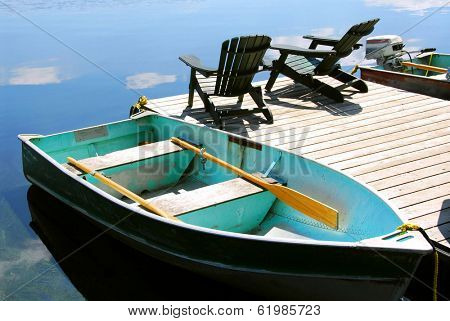 Paddle boat and two adirondack wooden chairs on dock facing a blue lake
