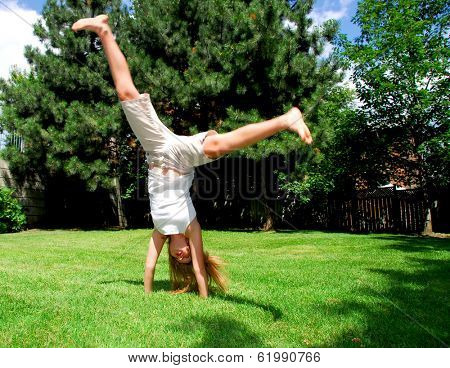 Young girl doing a cartwheel on green grass