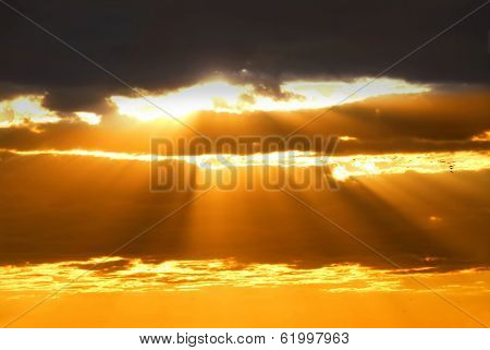 Rays of sun shining through the clouds at sunset