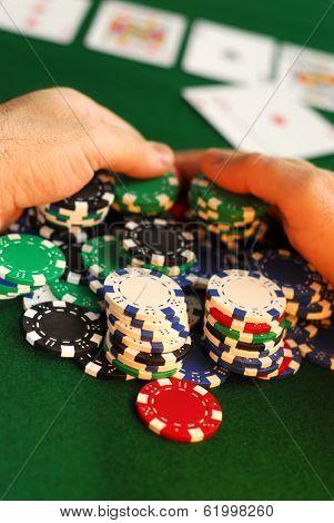 Poker player raking a big pile of chips