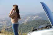 stock photo of beside  - Woman on the phone asking for assistance beside her crashed breakdown car in a mountain road - JPG