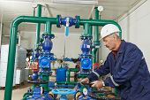repairman engineer of fire engineering system or heating system open the valve equipment in a boiler