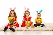 pic of bunny ears  - Three kids with bunny ears holding Easter basket and flowers and sitting in a row on carpet - JPG
