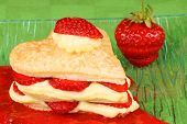 picture of custard  - Heart shaped strawberry and custard millefeuille on a strawberry sauce over a green background - JPG