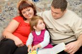 Married Couple And  Little Girl Read  Book In A Cozy Room poster