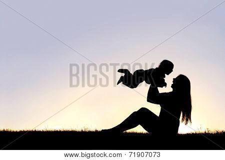 Silhouette Of Happy Mother Playing Outside With Laughing Baby
